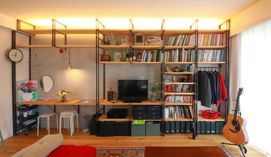 壁一面にスチールフレームを設置。本棚、TV台、収納、デスク、化粧台と様々な役割をこなす。