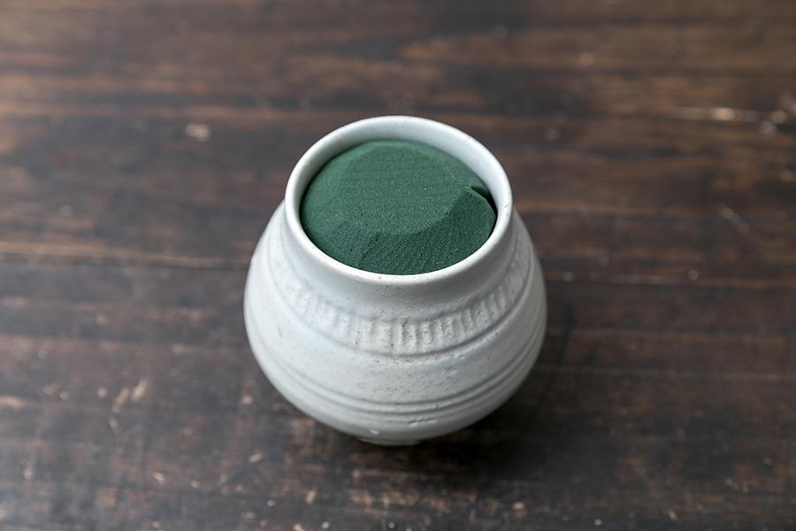 花器にオアシスをセットする。器の中で動かないようきっちりと詰める。