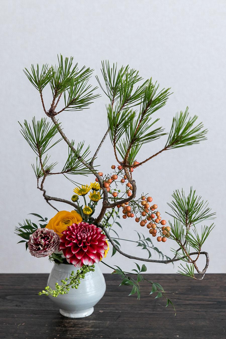 完成。材料は女松と南天。花は手前から、アオモジの蕾、赤いダリアと紫と黄色のラナンキュラス、奥にスプレー菊。