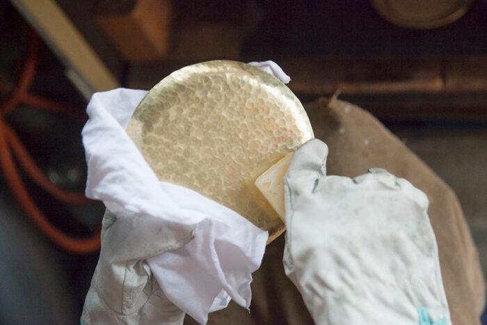 指紋がつかないよう乾いた布で押さえつつ、蜜蝋を全体に塗る。