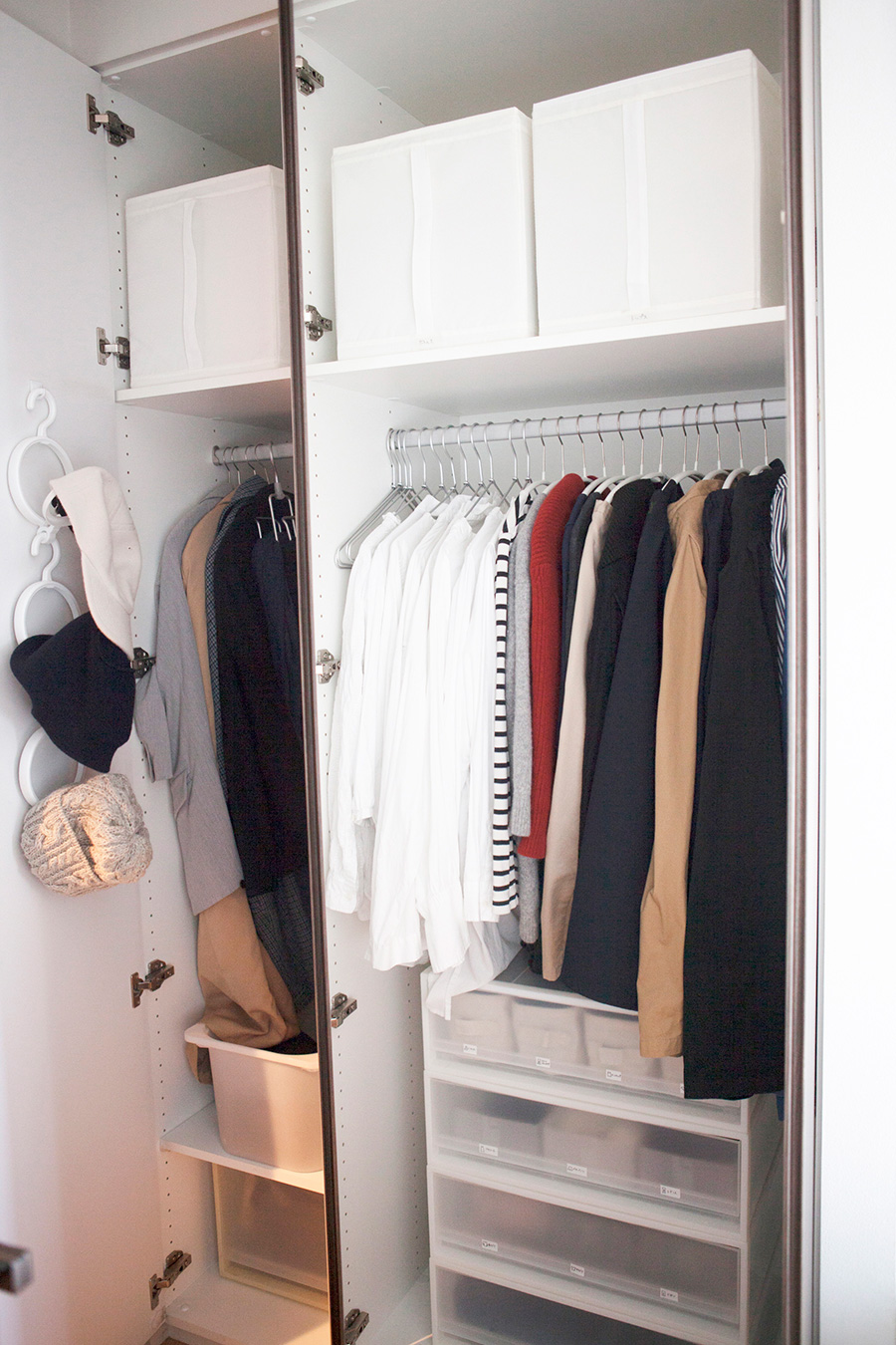 手前にトップスとボトムス、奥にはアウターとストールをかけている。季節毎に衣替えを行い、シーズンオフのものは枕棚の上のボックスに収納。