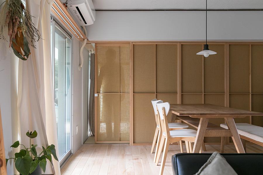 寝室とリビングを仕切る建具と壁の素材には、透け感のあるジュートを採用。仕切りつつも、開放的な印象を与える。