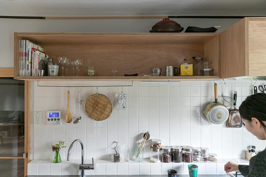 シンプルなデザインの造作の吊り戸棚。また、キッチン前面には、使い勝手のよい立ち上がりを設けた。