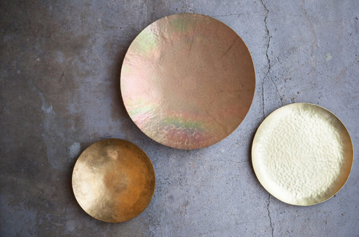 今回挑戦するのは、真鍮の小皿。形や鎚目模様などを自由にアレンジすることができる。右側が最後の仕上げまで終えた出来上がり作品。時間が経過すると左側のような風合いに変化する。中央は酸化膜を洗い流す仕上げを省いたもので、独特の色合いが楽しめ、この状態で終了することもOK。