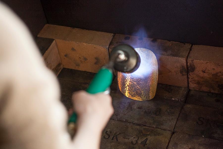 叩いて硬くなったプレートを、バーナーを使い、火にかけて柔らかい状態にする。約700〜800℃。火にかけすぎ、温度を上げすぎてしまっても、組織が変わり材料がボソボソになってしまうため、1分程して赤くなったら終了。