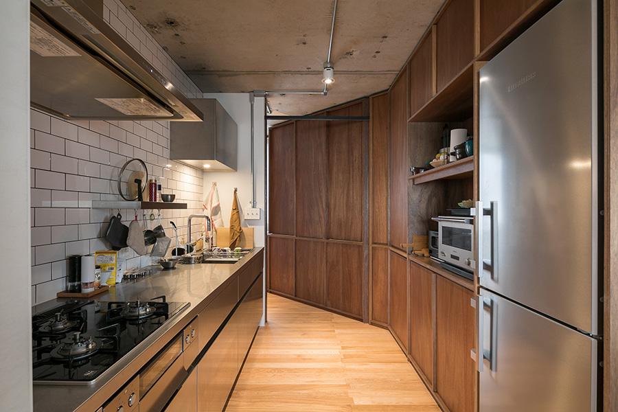 キッチンの先に寝室がある。変形四角形の家の形を生かし、ラワンの壁の先を期待させつつ、寝室はリビングから見えない絶妙な配置。
