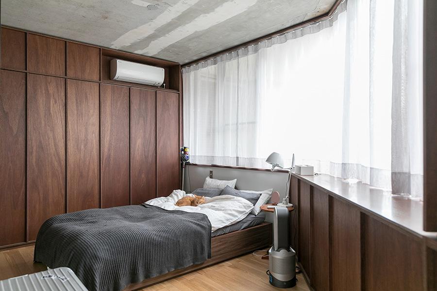 キッチンから続く同じデザインのラワンの壁は、寝室まで連続する。収納はこの壁の中に収まっている。