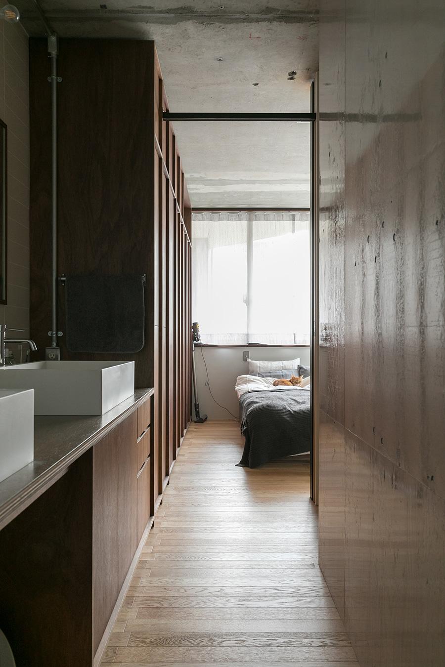 寝室から洗面所へ回遊。構造用合板を重ねた壁をツヤありの塗装にして光を反射させることで洗面所を明るくしている。