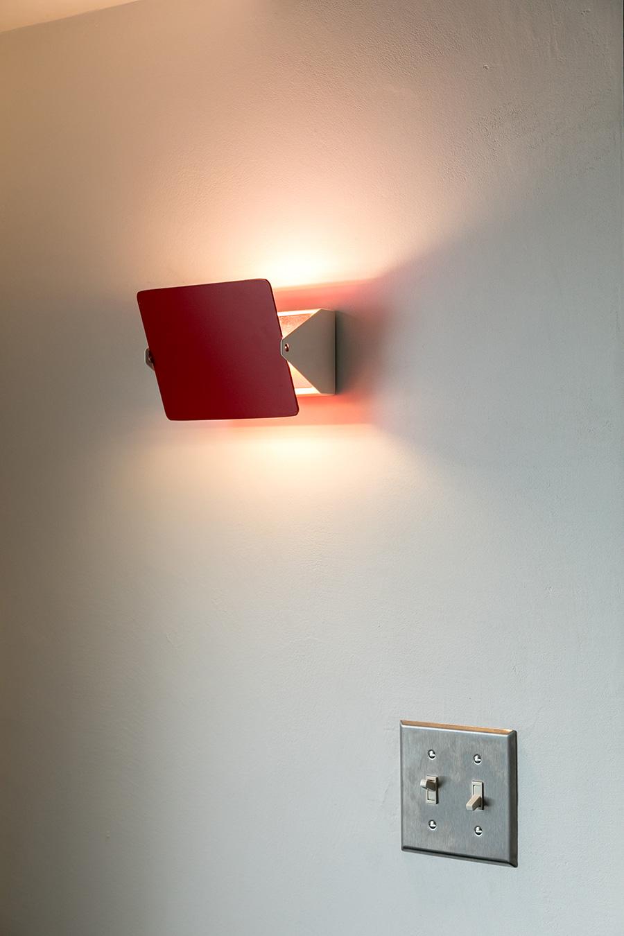 パネルの角度を変えることで上下の光の配分を調整できるシャルロット・ペリアンデザインの照明。赤の差し色が効いている。