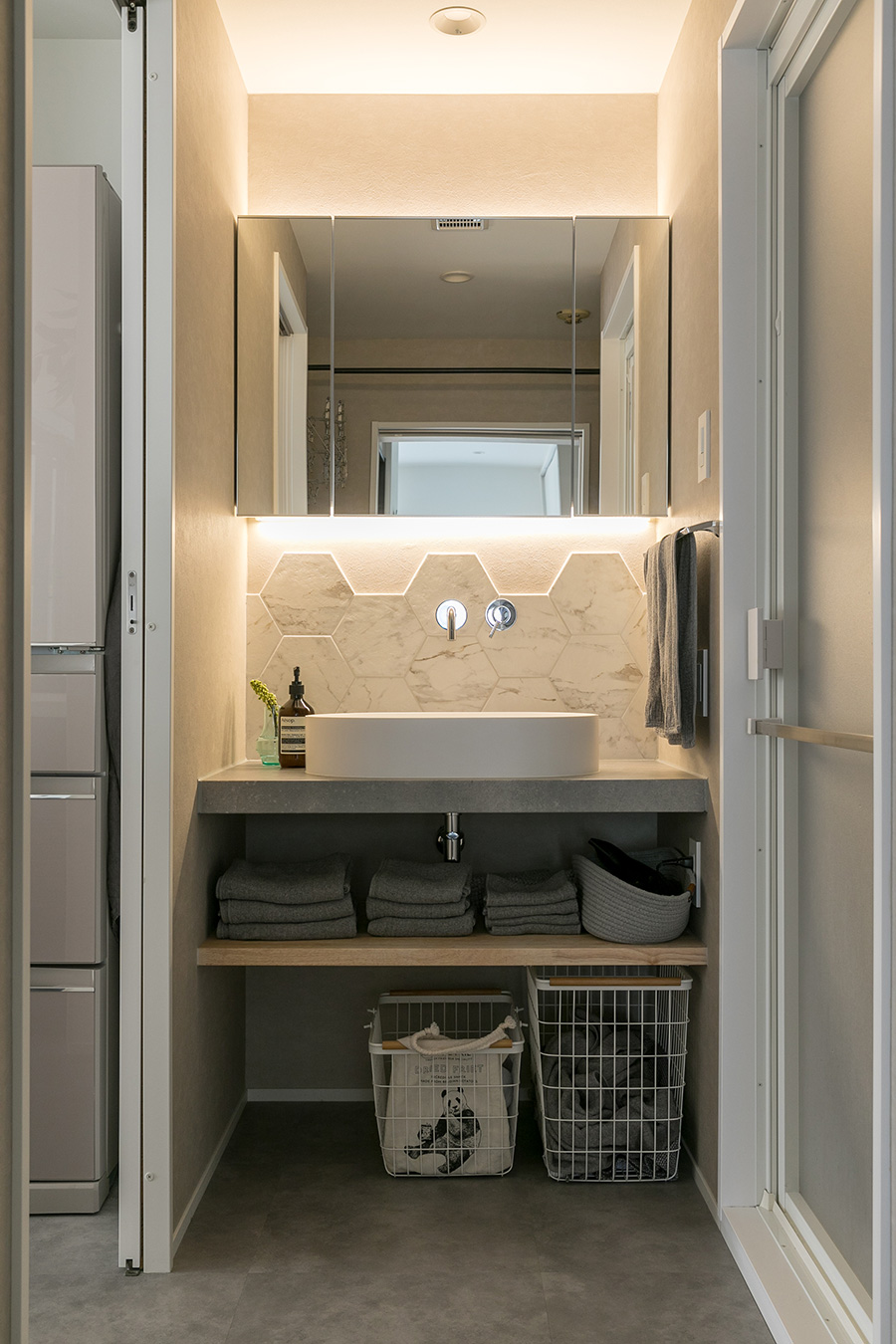 洗面台に貼られているのは名古屋モザイク工業社製のヘキサゴン型タイル。三面鏡下に設置された照明によりホテルライクな雰囲気を演出。