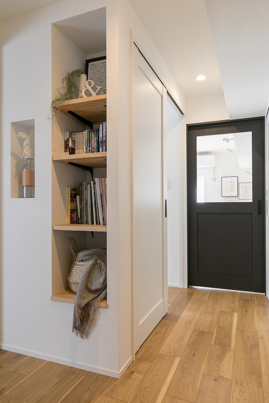 玄関からリビングに続く廊下。洋室の入口前には壁のスペースを利用した収納棚を設置。リビングの間にある引き戸にはガラスをはめ、ここにも広く見せる工夫がある。