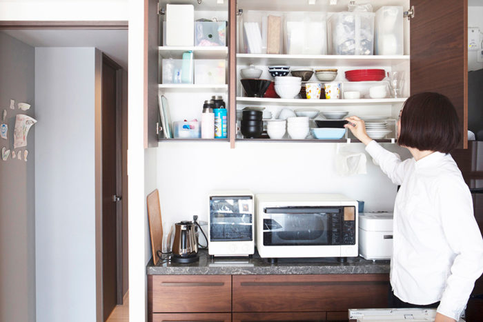 吊り戸棚には、手の届きやすい下の段から順に使用頻度の高い食器を。配膳のときも、食洗機で洗い終えた食器を戻すときも、最短の距離が確保されている。上の段にはたまに必要なお菓子の道具などを、中身が見える持ち手つきのボックスにアイテム毎に収めている。