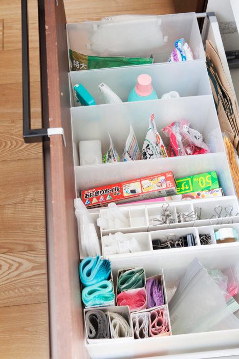 シンク下には引き出しが2段。下にある深い引き出しには、ファイルボックスにものを立てて収納。クリップなどの細かいものはボックスに引っ掛けられるポケットを使用。埋没しないので取り出しやすい。ポケットの下のデッドスペースには普段使わない排水口カバーを。