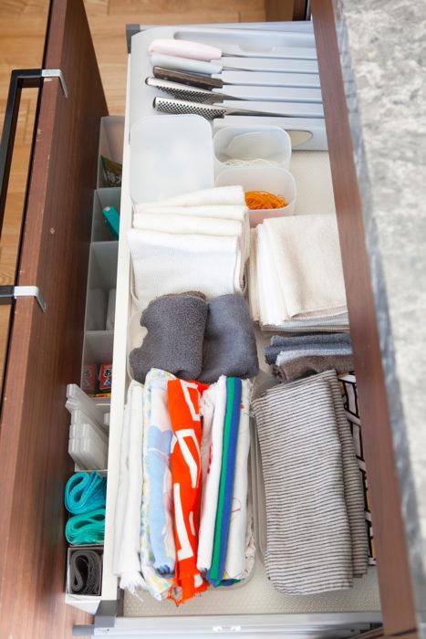 """上にある浅い引き出しには、よく使う布巾や包丁食洗機の洗剤などを収めている。引き出しを開けるとすぐ手が届く""""10cm""""の距離が大事。小分けのケースでアイテムに分け、ごちゃつくのを防いでいる。"""