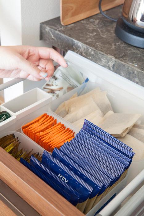 毎日飲むお茶は袋から出して種類に分けて小分けケースに。個包装のない麦茶パックのみ、フタつきボックスに入れて湿気を防いでいる。麦茶パックは予め切り離しておき片手で取り出せるように。