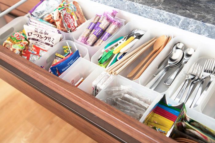 カトラリーなどを小分けケースに分類。子ども用カトラリーを入れたケースにその日使う大人用のお箸やカトラリーを入れ、まとめてダイニングテーブルへ。お菓子類はひと目で分かるようにしておくことで、買い過ぎ、食べ忘れも防げる。