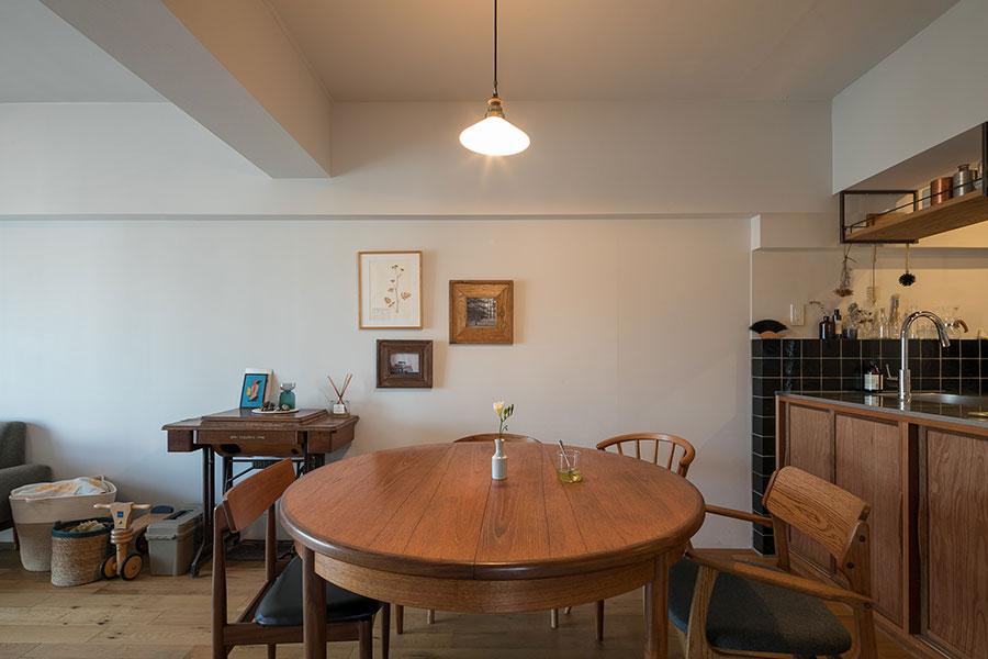 「ダイニングテーブルは丸形のものを置きたいと思っていました」。イギリス製のアンティークで、楕円に広げることもできる。「壁にかけた3枚の額は私と夫のものです。好みが似ていたので組み合わせて飾ることができました」