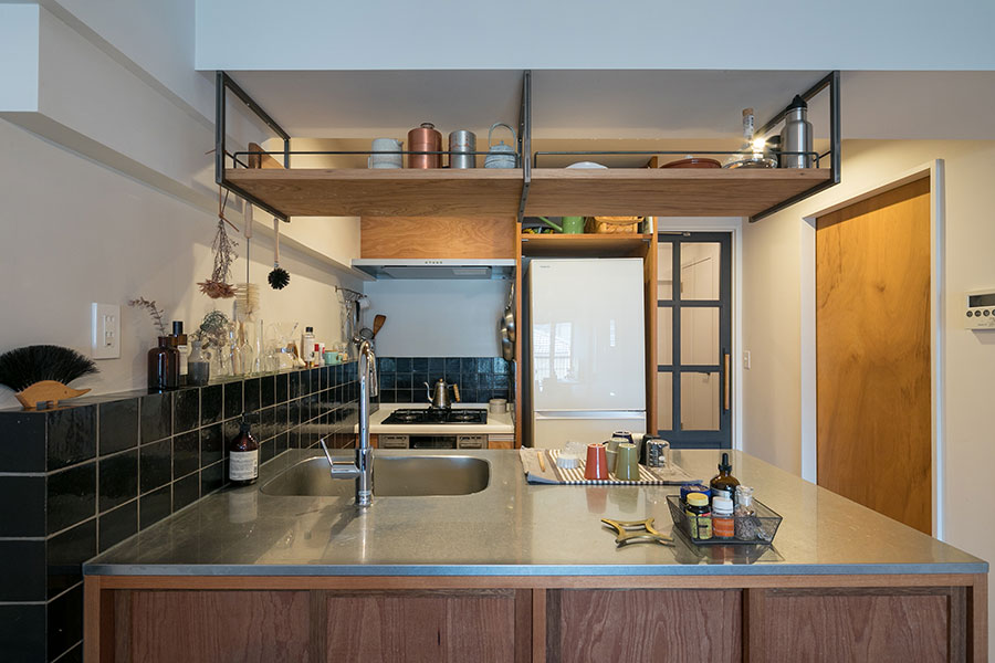 『toolbox』のサイズオーダーができるステンレス天板のキッチン。「手持ちの大皿が入る幅+反対側に電子レンジが置ける奥行きを確保しました」。吊戸棚はアイアンで造作したものに棚板を渡し、『toolbox』のハンガーバーで落下防止。