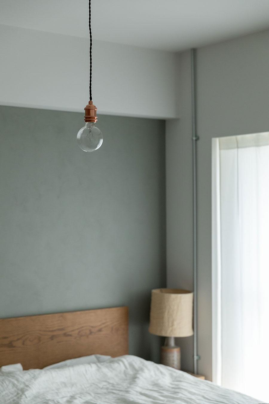 寝室のグレーの壁面はDIYで塗装。ペンダントライトは『BRID(ブリッド)』。のもの