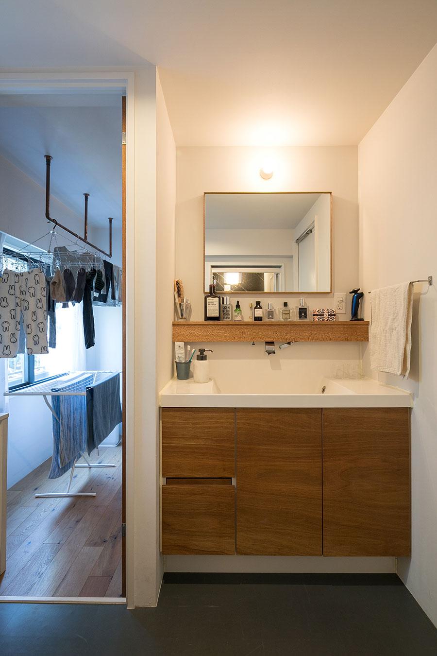 洗面室から家事室へ直接入れる動線を作った。洗面台は既存のシンクを使い、鏡とラワン材の収納扉を替えました」