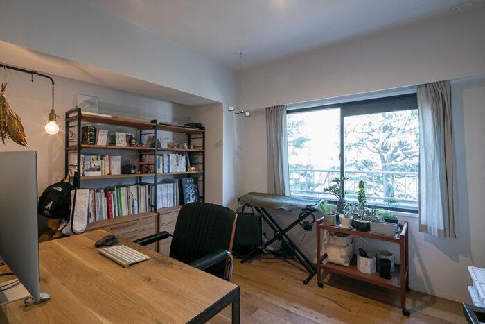 壁を動かして広げた洋室は、将来は子ども部屋に。「書棚の高さはリビングに移動することも考えて決めました」。デスクは『toolbox』のアングルフレーム脚とフリーカット無垢材を組みあせて作ったもの。窓から見える公園の緑が気持ちいい。
