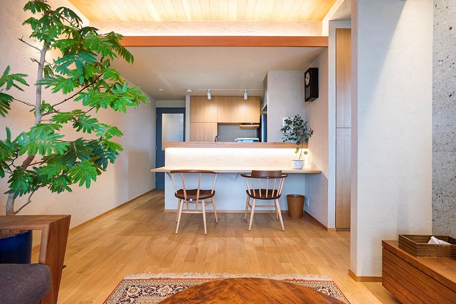 リビングからキッチン側を見る。キッチンはあえて天井をリビングよりも低くすることで、空間に変化をつけている。