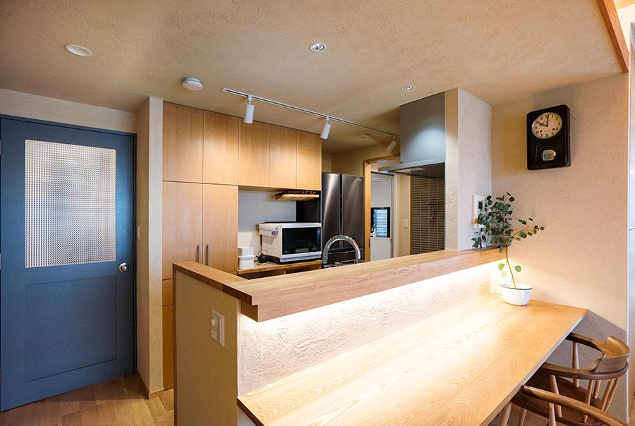 もともとあった吊り収納を取り外してオープンなカウンターキッチンに変更。間接照明が効果的に用いられている。