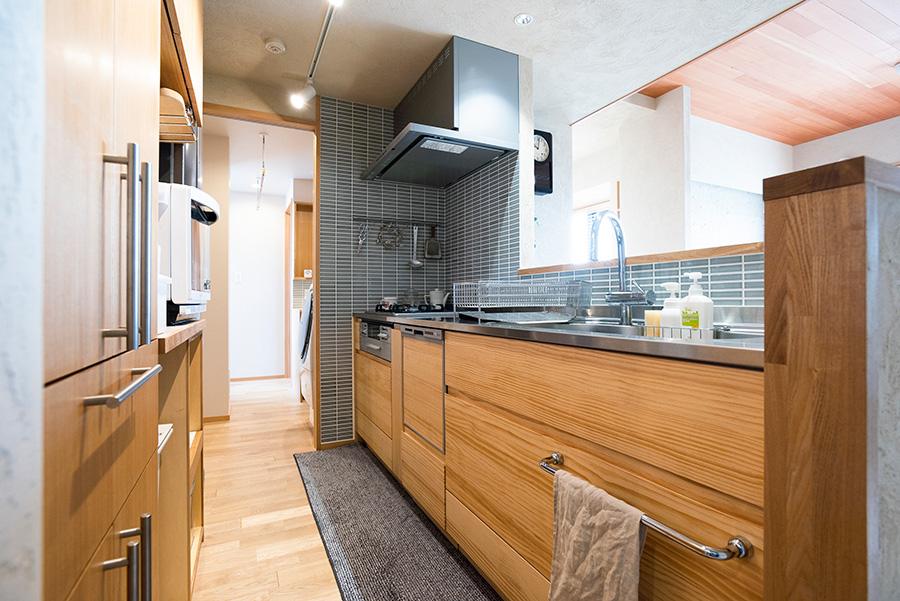 脱衣所、バスルームに隣接したキッチン。持っていた収納に合わせて棚を造作してもらった。パイン材を使ったキッチン台はWOODONEのもの。