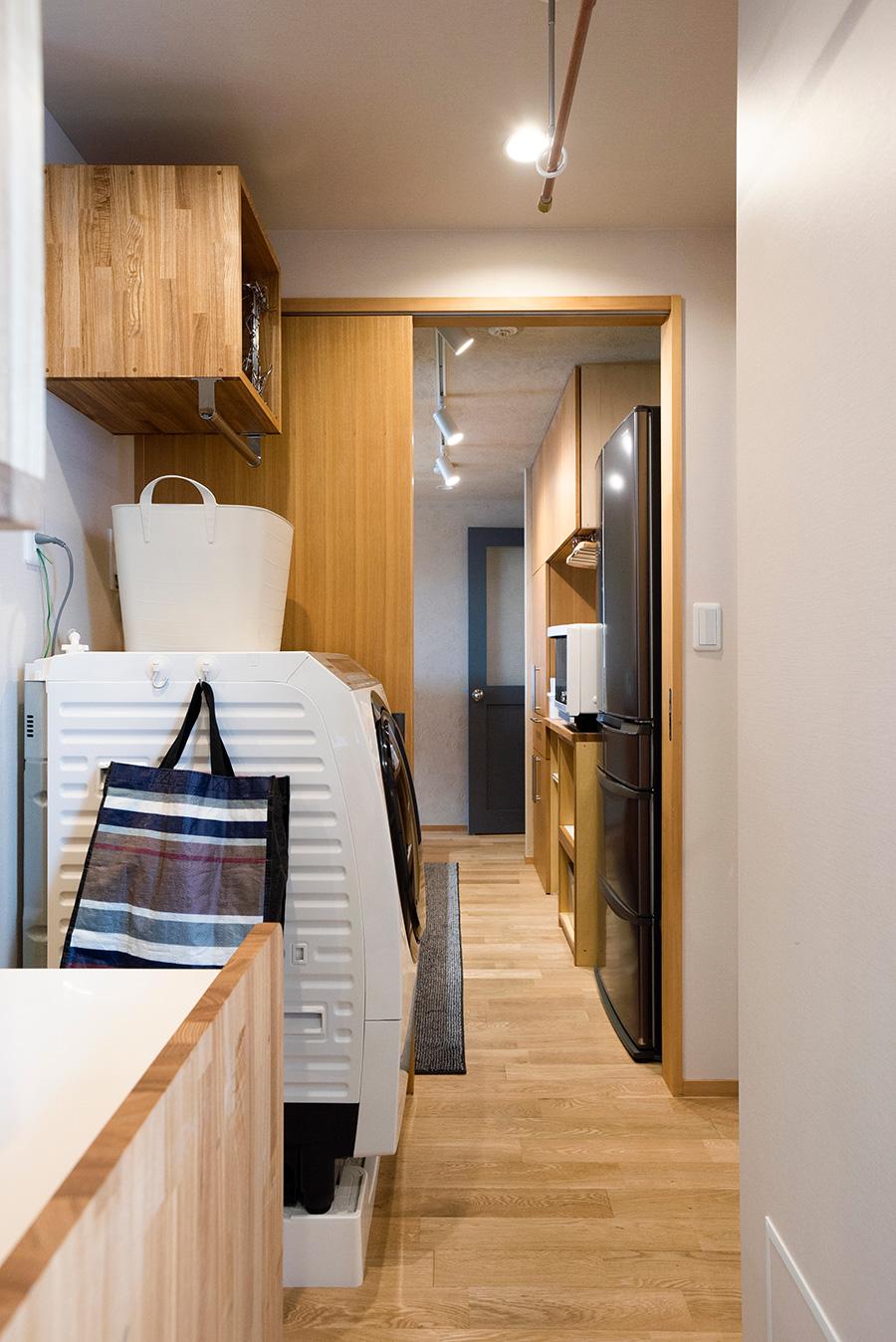 脱衣所の横は洗濯機置き場、そしてキッチンへと続き家事動線を確保。洗濯機上に設けた棚にはバーも取り付けた。