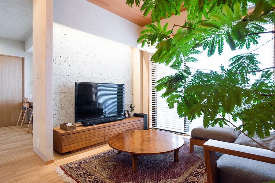 テレビコーナーを造作。大谷石を壁にあしらい、間接照明で光を当てている。ローテーブルにしている台は、和彦さんのお祖父さんが手作りしたもの。脚を切り塗装をして使用。