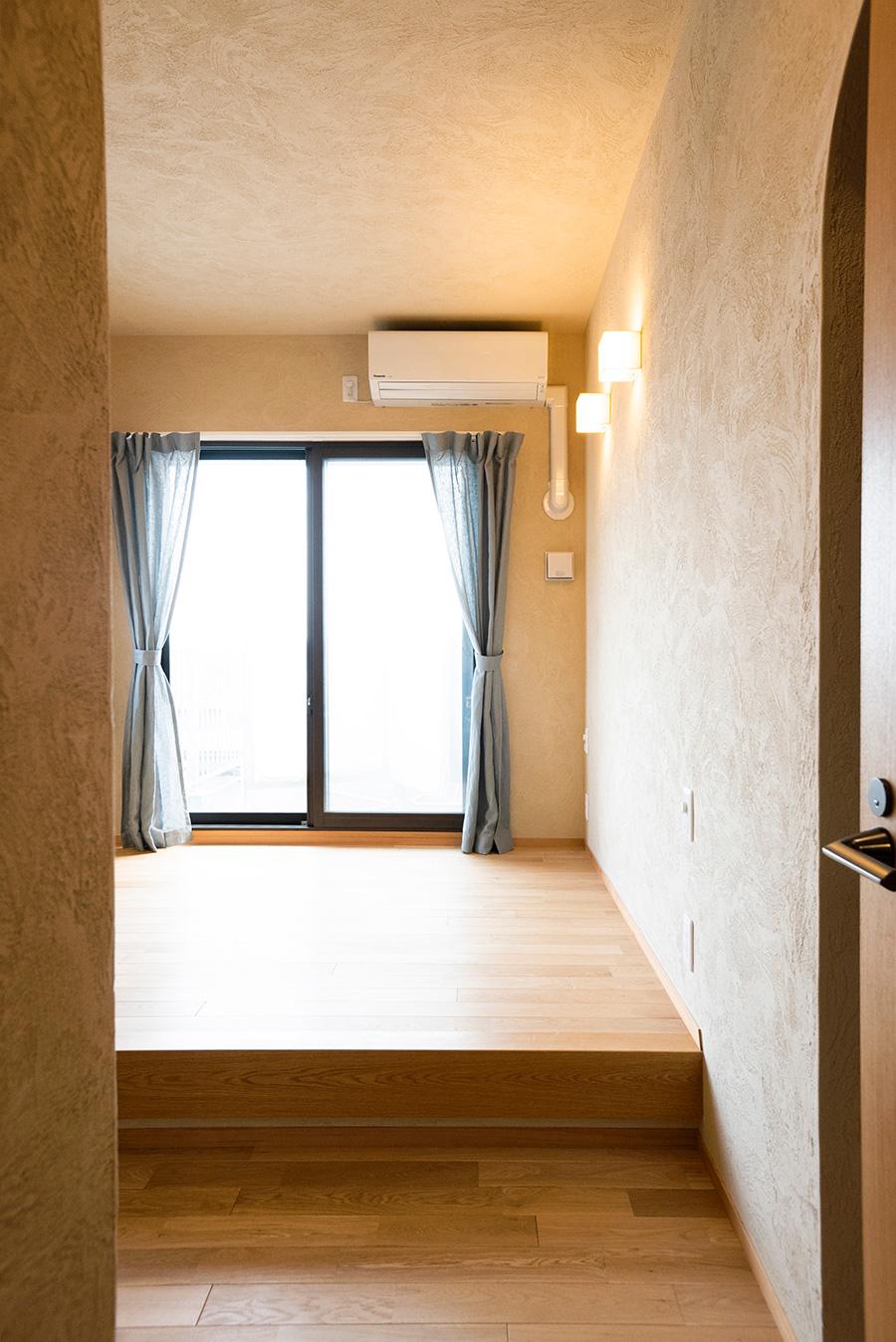 ルーフバルコニーに面した寝室は、1段上げて小上がりに。「布団を敷くことを考えて小上がりにしました。段差があると散らかりにくいのも利点です」(奥山さん)。