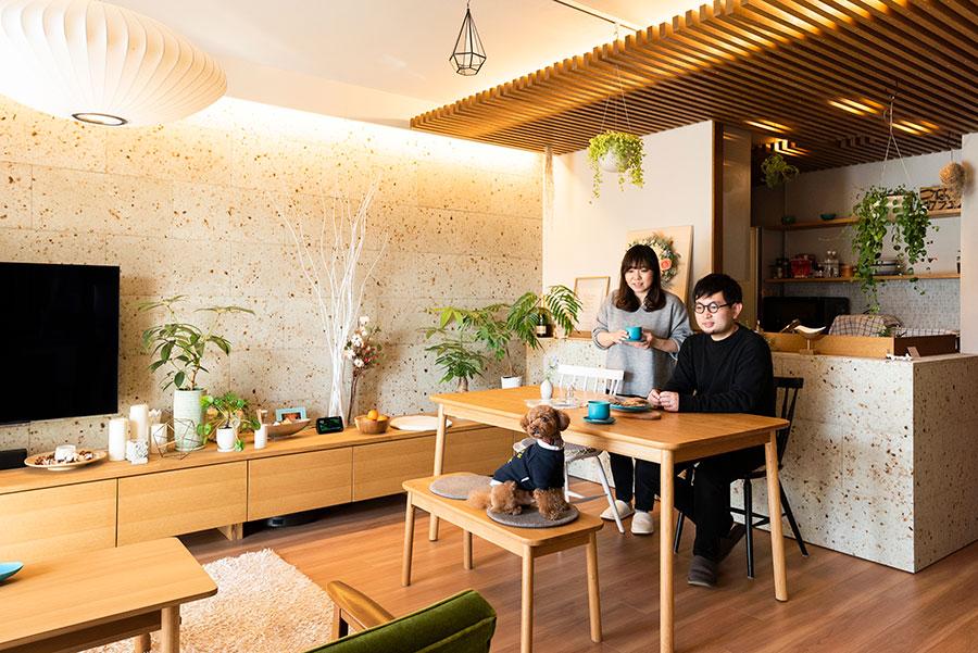壁やキッチンの大谷石、天井のルーバーが自然に包まれている雰囲気を与える。