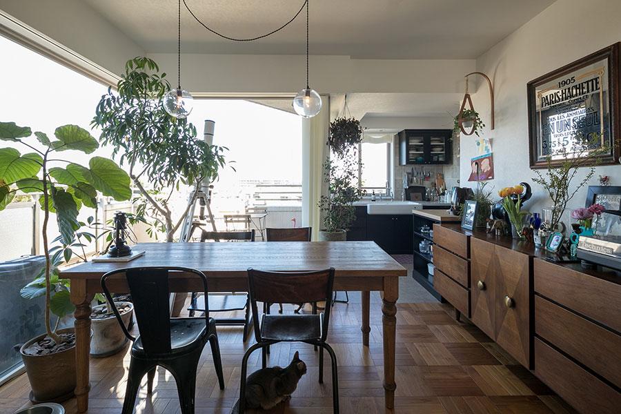 L字型の大開口によって明るく開放的なダイニング。テーブルはご主人の知り合いの職人による手作りによるもの。右側のヴィンテージチェストはご主人のお気に入り。代々木上原にあるインテリアショップ「ARKESTRA(アーケストラ)」で出会ったという。