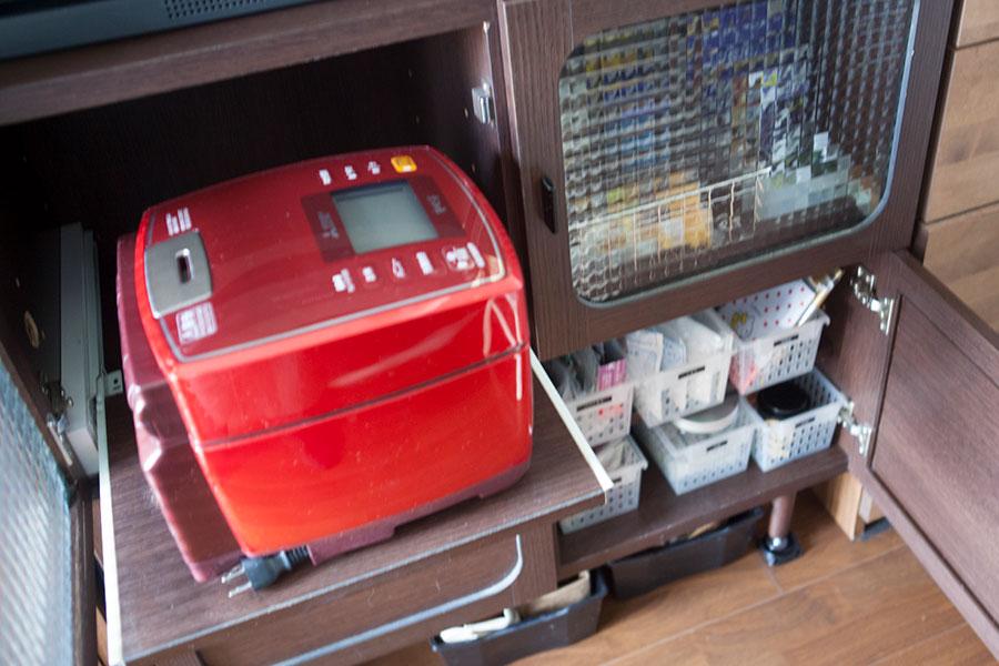 炊飯器が棚板ごと引き出せるように、スライドを取り付けた。下の段には薬などを、100均のケースで分けて収納。