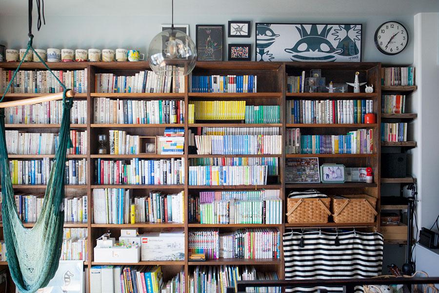 LDKの一面を占める本棚。低い位置には子どもの本など、家族別にゾーン分けされている。さらに子どもの本には背表紙にマスキングテープを貼り、図書館のように戻す位置が分かる仕組みをつくっている。