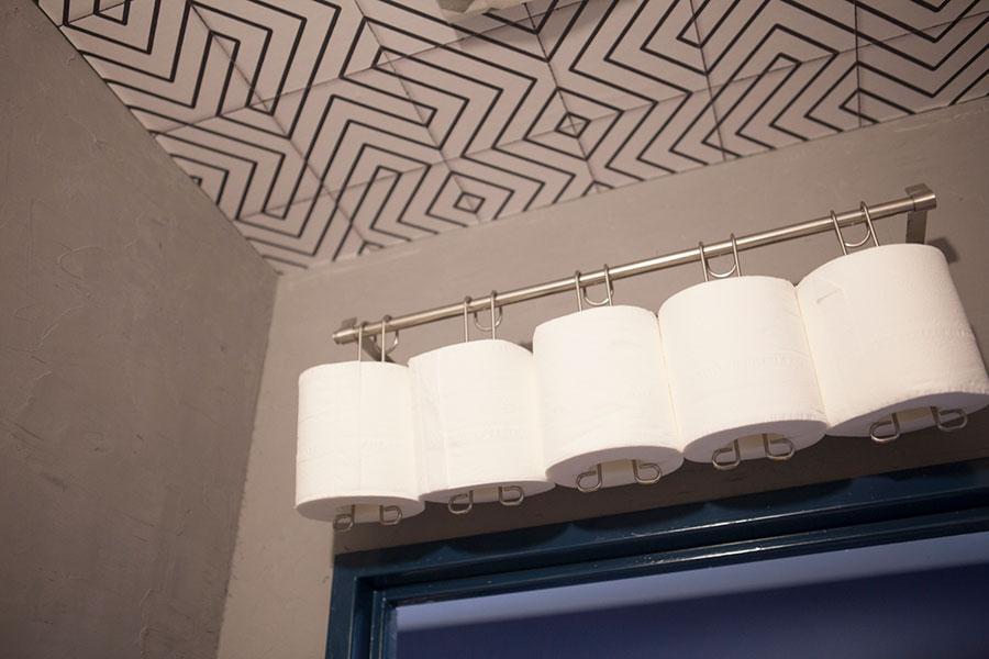 収納を付けなかったトイレには、DIYでペーパーホルダーを。天井には壁紙を貼った。