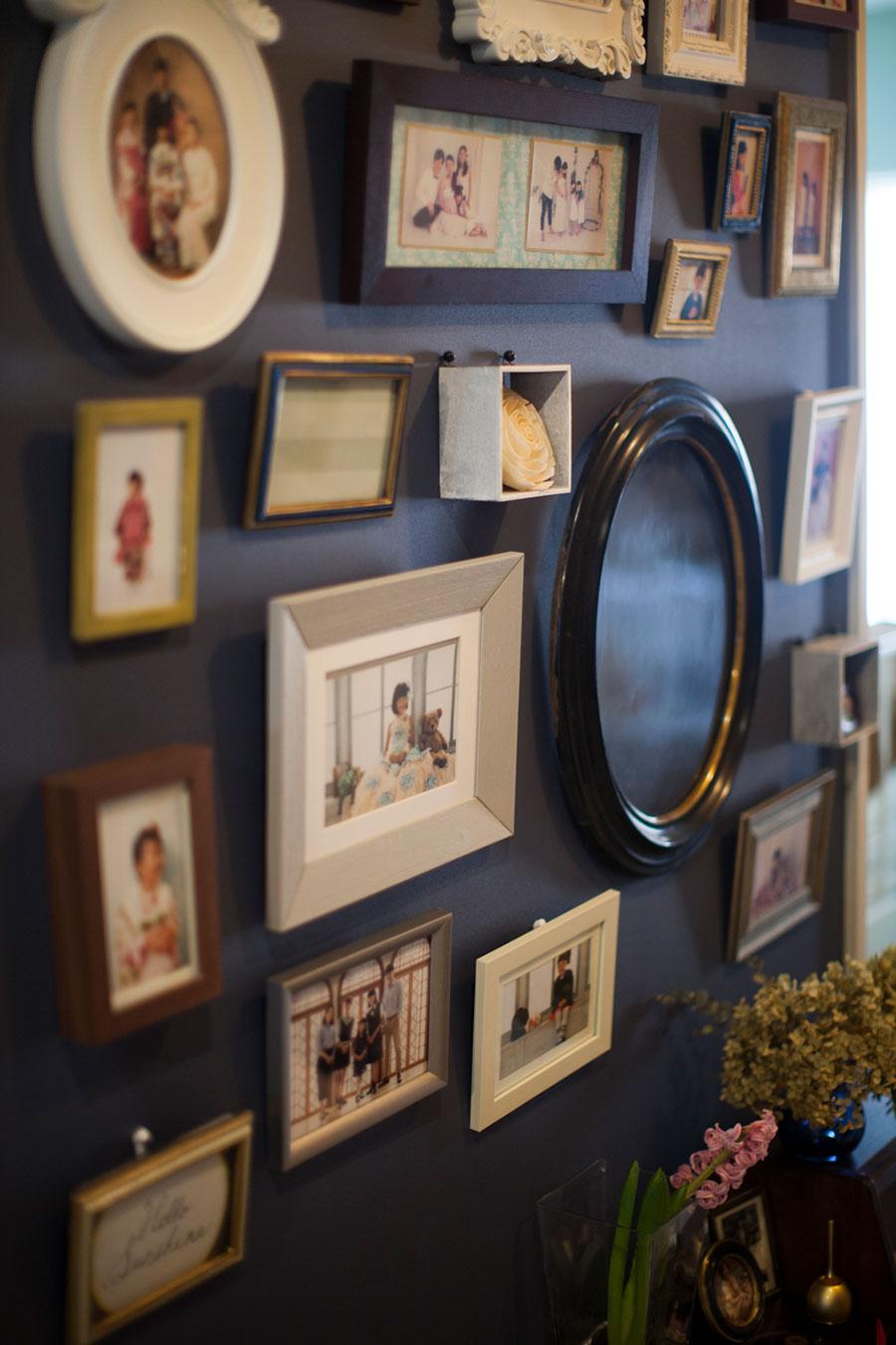 家族の思い出の写真を壁一面に。玄関を開けると現れるこの場所が、岡本さんいちばんのお気に入り。