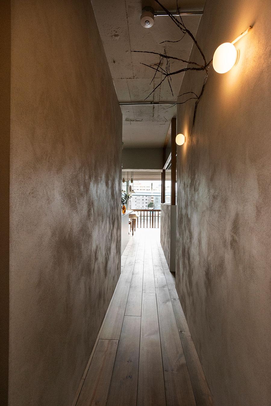 ポーターズペイントを塗った壁に挟まれた廊下が、リビングへと導く。
