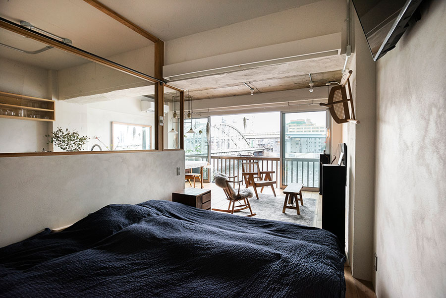 個室として仕切ることを避け、オープンにしたベッドルーム。ガラス窓にはカーテンレール、リビング側にはロールカーテンもあり、必要な場合は閉じることもできる。