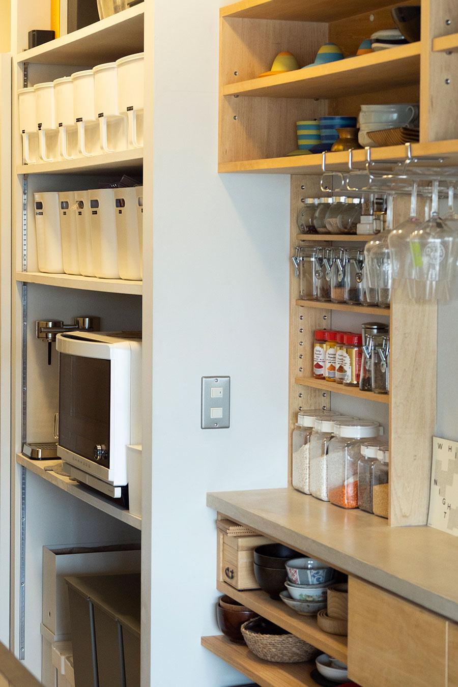 夫・邦夫さんがよく作るカレー用のスパイスが並ぶ棚。収めるもののサイズを考えて造作した。その向こうは見事にオーガナイズされたパントリー。