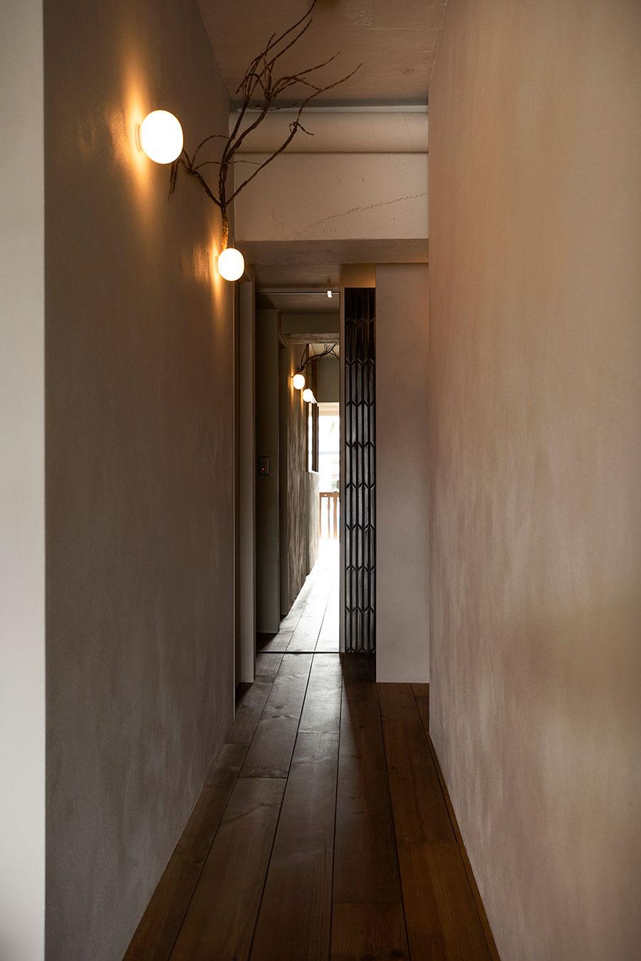 ニュアンスのある壁に包まれる廊下。突き当たりのトイレのドアを鏡にすることで、奥行き感を生んでいる。壁を照らす照明はFLOSのもの。