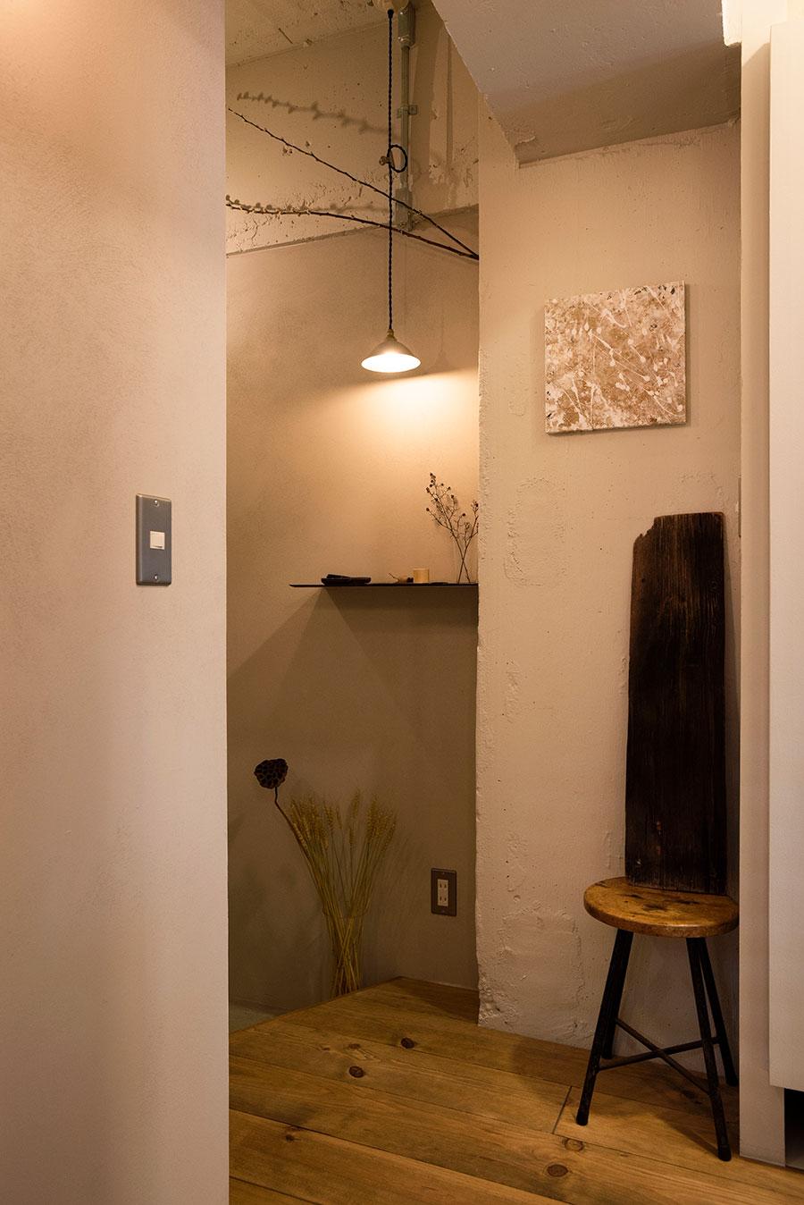 アートや植物、古家具、照明で演出した玄関ホール。妻・けいこさんのセンスが光る。柱や梁、壁の塗り分けが微妙なニュアンスを出す。