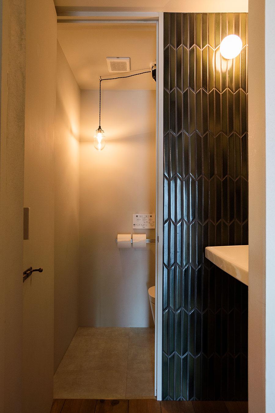 トイレのペンダントライトの位置にもこだわった。洗面のレトロな雰囲気のタイルは平田タイルのもの。