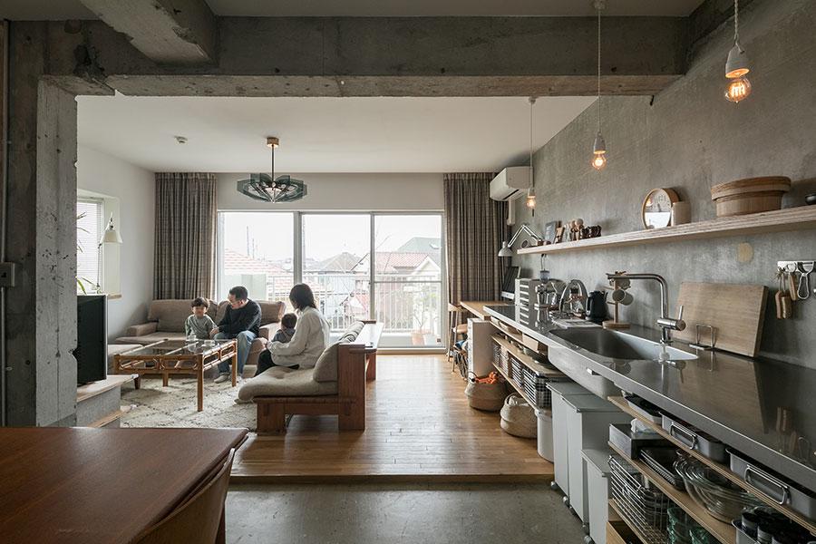 壁付けのオープンキッチンは作業スペースもたっぷり。窓側はリモートワークで活躍したデスクスペースになっている。リビングの照明とカーテンは、以前ここに住んでいた方から譲り受けたもの。