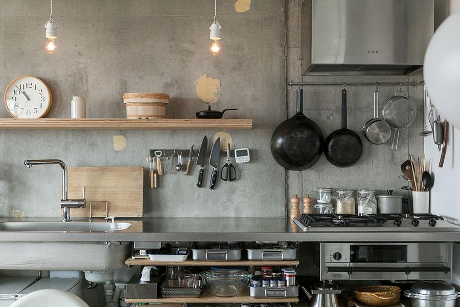 ステンレスのキッチンとコンクリート現しの壁、棚の積層の小口の組み合わせが美しい。ペンダントライトはフランスの陶器製のもの。「棚の上にあるおひつは、父の友人の桶職人が作ったものです。新築祝いにいただきました」
