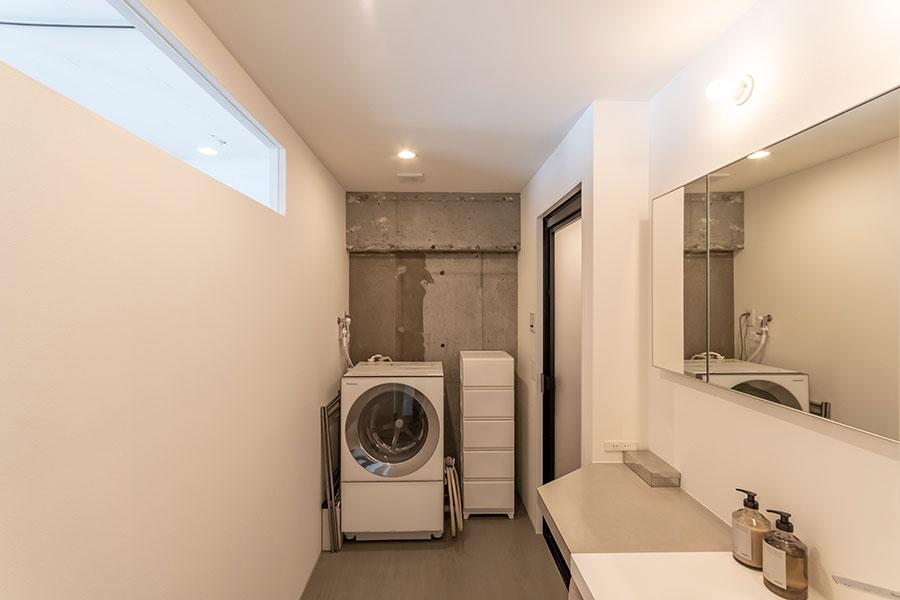 モルタルと白壁で構成されたモノトーンな洗面所。