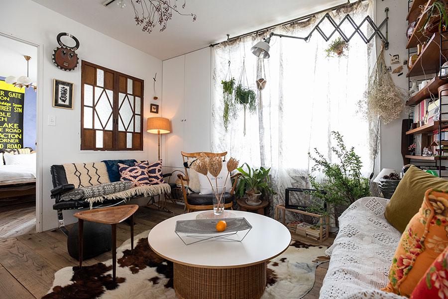 グリーンやドライフラワー、オブジェで彩ったリビング。剣持勇のラタンのローテーブル、オリヴィエ・ムルグがデザインしたエアボーン社のソファーなど、この部屋に合わせて入居後に購入した。