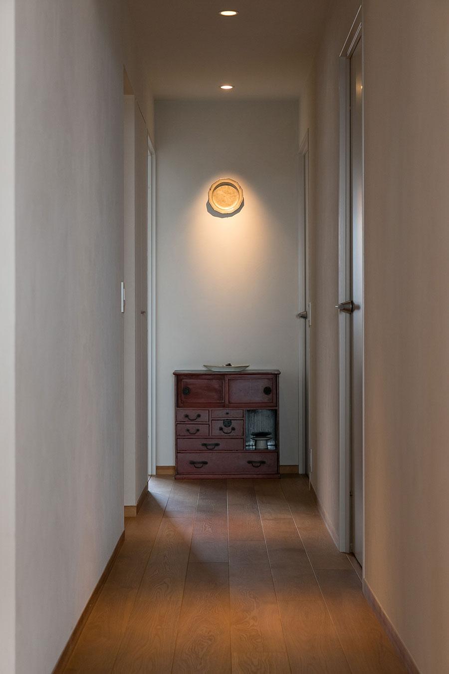 廊下の先に置いた和箪笥は、漆職人だったおじいさまの作品。壁にかけた皿はフランスのアンティーク。「皿に入った傷が絵のように見えます」。スポットライトを当てて演出。