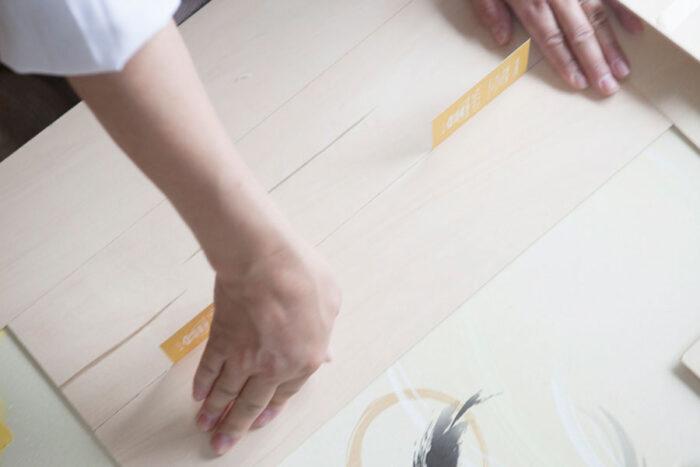ドアの下のところの縦に並べる板を張る。少し隙間が空くよう、名刺などを1枚かませて張っていくのがポイント。