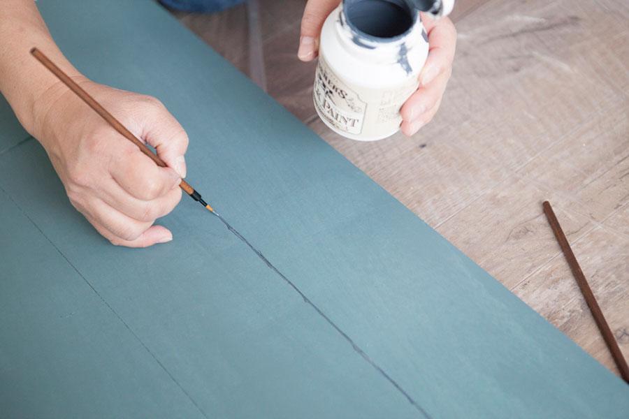 縦に並べた板の際に細い筆で濃い色を入れ、奥行き感を出す。